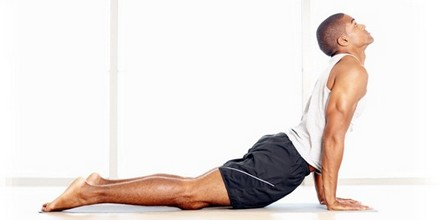 Profile view of a healthy young African American guy doing stretching exercises on a yoga mat
